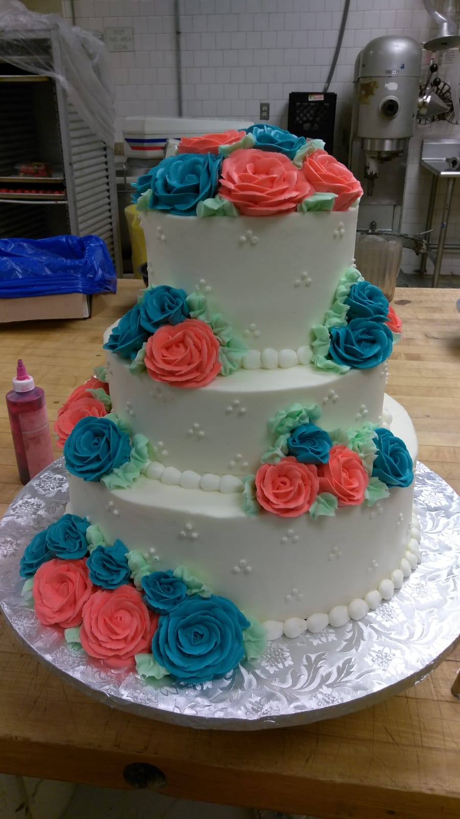 Pink and blue roses on white tiered cake