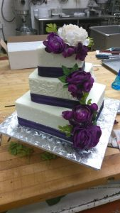 Square offset wedding cake with purple flowers
